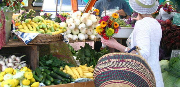 a farmers market shopper with flowers and summer produce